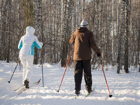 Two elderly people go skiing with ski poles in the winter park. Good bright day. Healthy lifestyle. View from the back.