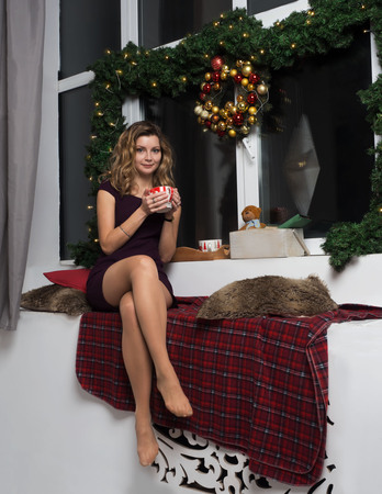 A beautiful girl in a dress sits near the New Year's window and drinks a hot drink. Decoration of branches of a Christmas tree, garlands and snow outside the window. Banco de Imagens