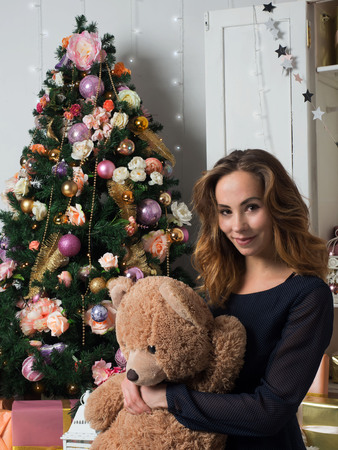 A young girl sitting in front of a Christmas tree and hugs a toy bear. The spirit of Christmas and a sense of celebration.