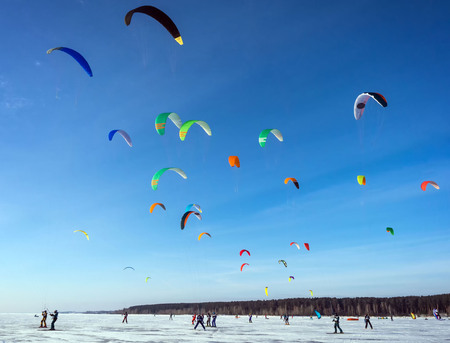 Kitesurfing in the winter on snowboard or ski. Skating on the ice in the wind. Beautiful colored sails.