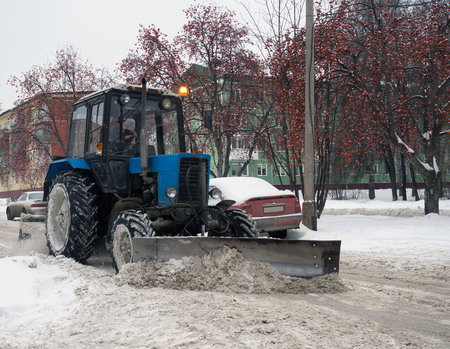 Blue tractor cleaning the streets of large amounts of snow in city after snowfall. A snowplow clearing a road. Winter time concept. Banco de Imagens