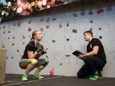 NOVOSIBIRSK, RUSSIA - DECEMBER 18 2017: The instructor takes the performance of the crossfit complex squatting with the weight of a sports girl. Deep squatting. 에디토리얼