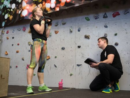 NOVOSIBIRSK, RUSSIA - DECEMBER 18 2017: The instructor takes the performance of the crossfit complex squatting with the weight of a sports girl. Many repetitions, heavy weight.