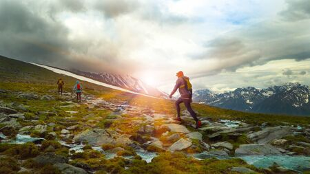 Group of running on a mountain trail. Backpacks for running behind his backs and poles in hand. Rays of the rising sun. Soft blur effect.