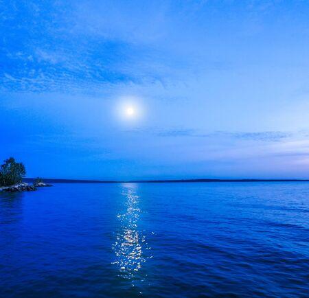 Moon in night sky over moonlit sea water. Travel background. Banco de Imagens