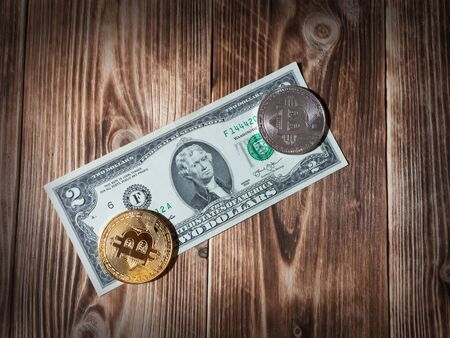 Physical version of Bitcoin, new virtual money, and banknotes of two dollar on a wooden background. Conceptual image for worldwide cryptocurrency and digital payment system.