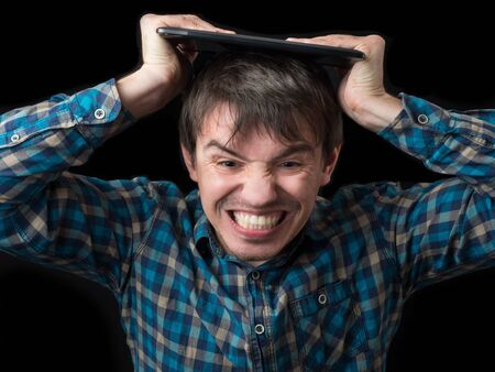 The enraged young man breaks the tablet on his head. Bad device. Disappointment and anger. Stock Photo