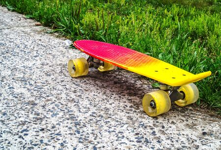 A red-yellow penny board with yellow wheels on the edge of the asphalt and grass transition. Style of freedom and travel in the summer. 스톡 콘텐츠