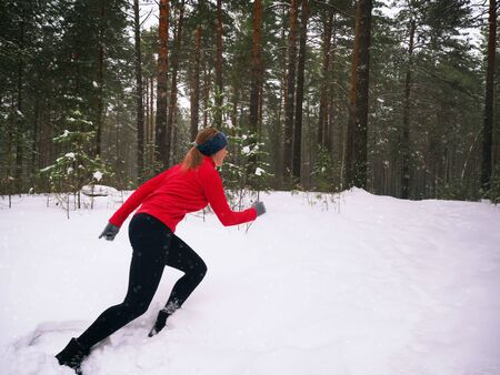 Young woman fitness model running in a city park. Runner jogging in snow. Winter running exercise. Snow is falling.