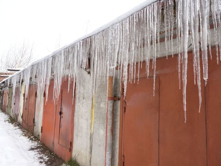 Numbers of ice icicles hang under the roofs of the garages. Danger of falling and injury. 스톡 콘텐츠