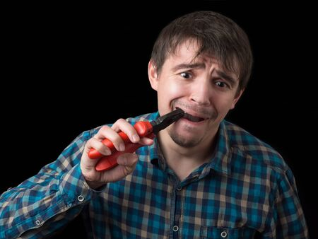 A young handsome man with a beard and mustache pulling out his tooth with pliers. Studio shot against black background. 스톡 콘텐츠