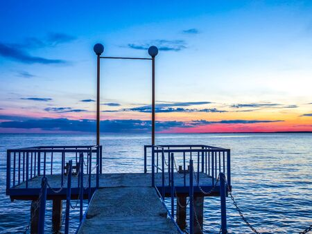 Old concrete pier with chains. Sunset red blue sky. Banco de Imagens - 131527737