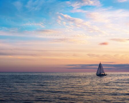 Beautiful gold sunset with a sailboat sailing. Air clouds of different colors.