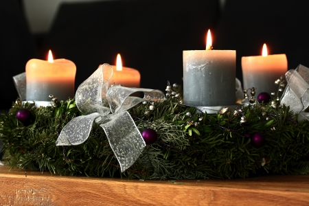 Advent wreath with burning candles on an oak table Stock Photo