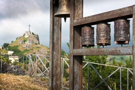 Prayer wheels and christian cross on a hill in Italy photo