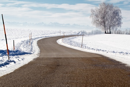 Country road in winter with view of the alps photo