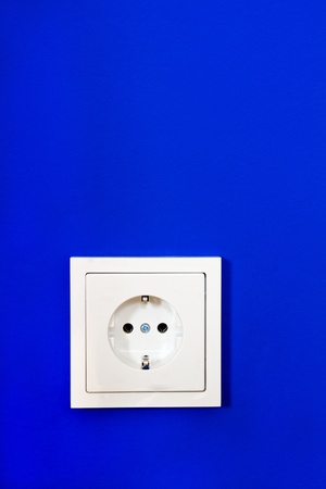 Electrical outlet on blue painted wall photo