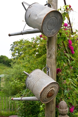 neighbourly: Two watering cans hanging on a wooden pole Stock Photo