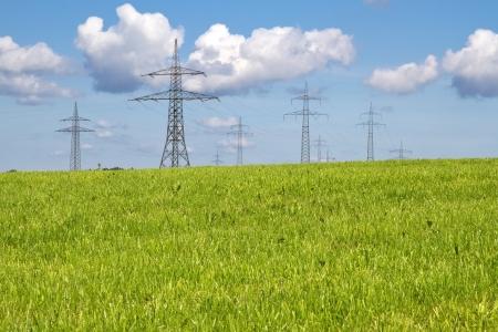 torres de alta tension: Torres de energía en un prado en primavera