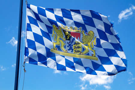 Streaming Bavarian flag against blue sky Stock Photo