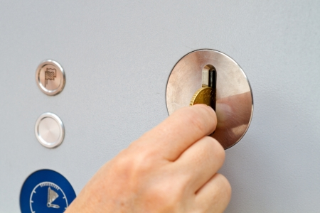 Hand die een Euro muntstuk in een machine Stockfoto