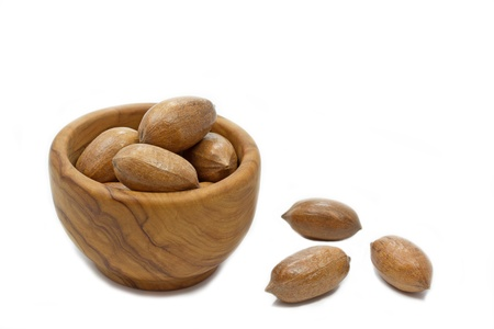 whole pecans: Pecan nuts in a wooden bowl on white background