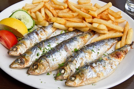 sardines: Grilled sardine fish and french fries served on a plate in a pub