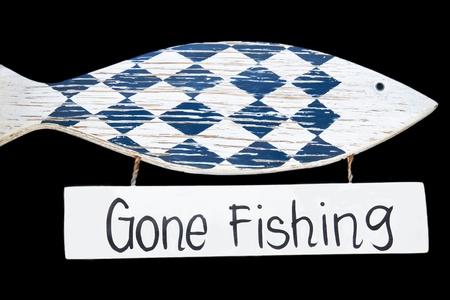 short phrase: Wooden gone fishing sign, isolated on black background Stock Photo