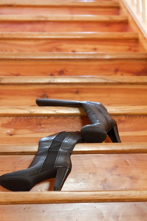 Wood stair with black womens boots photo
