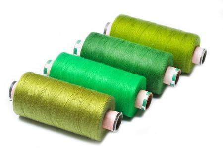 Four bobbins of thread on white background