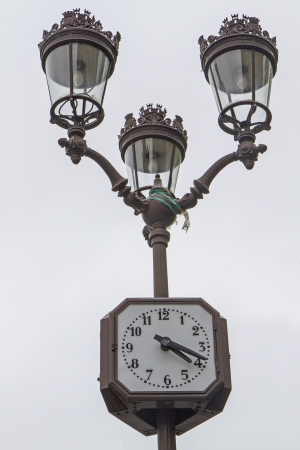 Metallic retro lamppost with clock in Paris, France photo