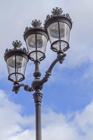 Metallic retro lamppost in Paris, France, against the sky photo