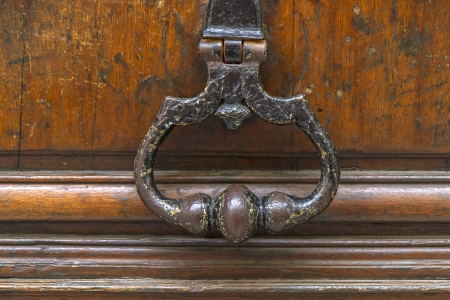 Old metal door handle and knocker on wooden door photo