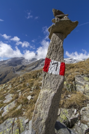 Tall stone marking a hiking trail in northern Italy photo