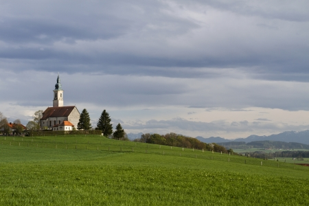 prayer tower: Typical bavarian church with view to the alps Stock Photo