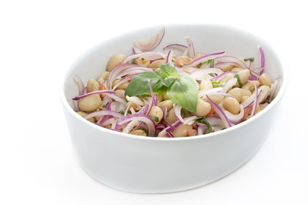 Salad with white beans and onions on white background photo