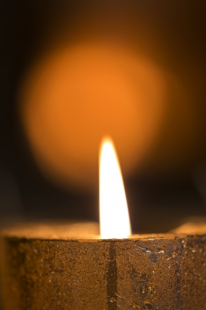 Single Burning candle in warm light photo