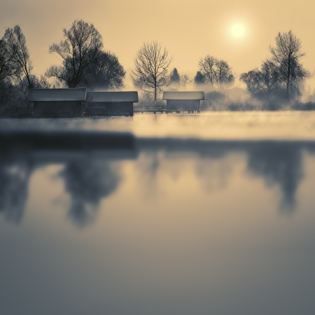 Boathouses on a lake in winter with fog and sun photo