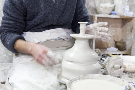 Potter at work in a pottery in Morocco photo