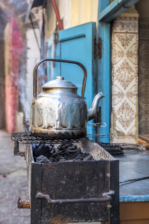Single silver tea pot in a Moroccan alley photo