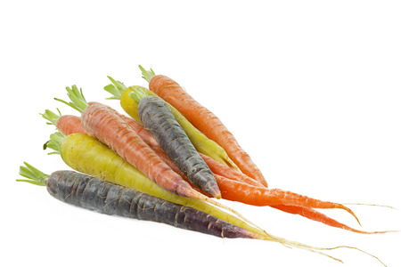 Raw carrots with different colors on white background