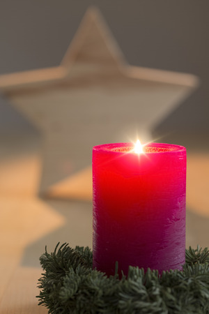 Burning candle with star in the background photo
