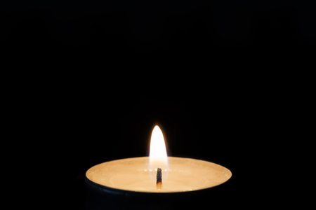 One burning tealight in darkness, closeup