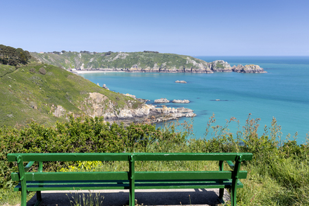 guernsey: Bench overlooking south coast of Guernsey island, UK, Europe Stock Photo