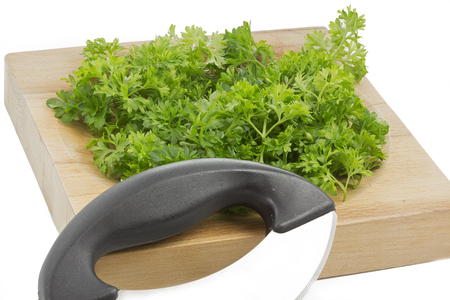 Fresh parsley on a wooden chopping board, isolated Stock Photo