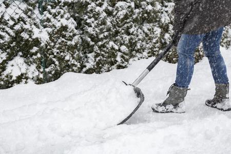 shoveling: Woman shoveling snow on pavement