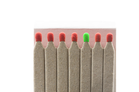 Matches with red and one green heads, isolated on white background Stock Photo