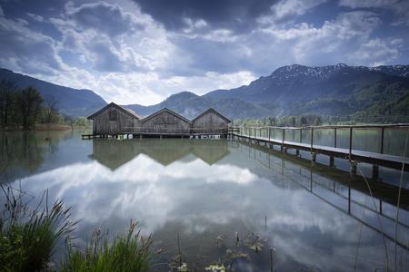 Jetty and boathouses at lake Kochelsee, Bavaria, Germany