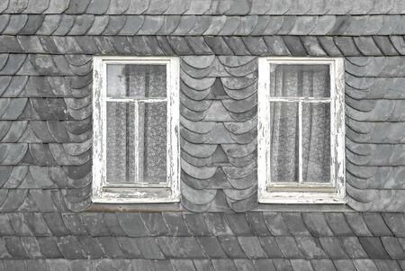 Slate tiles with two old windows on a facade of a typical home in Thuringia, Germany