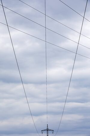 High voltage pylon with cables and dramatic sky Imagens